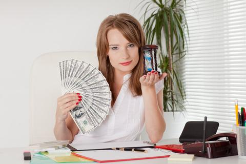 Mulher segurando dinheiro numa mão e uma ampulheta na outra